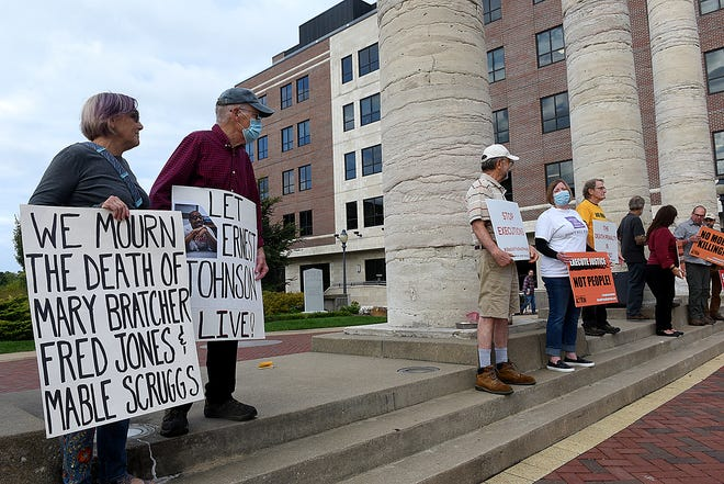 A dozen people hold signs on Tuesday in front of the old Boone County Courthouse columns protesting the execution of convicted murderer Ernest Lee Johnson. Gov. Mike Parson on Monday declined to grant clemency to the death row inmate who killed convenience store workers Mabel Scruggs, Mary Bratcher and Fred Jones during a 1994 robbery in northeast Columbia.