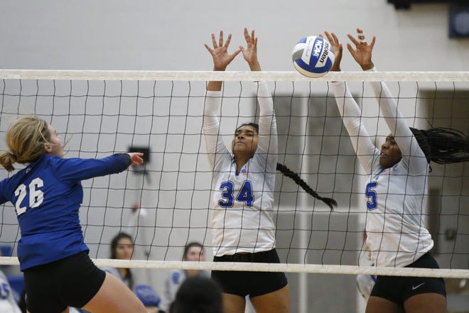 Liberty's Michelle Ezenekwe (5) and Mitha Hatwar (34) go up to block Hilliard Bradley's Kali Barber earlier this season. Ezenekwe, a senior, has battled back from an ACL injury that occurred during her sophomore season and required two surgeries.