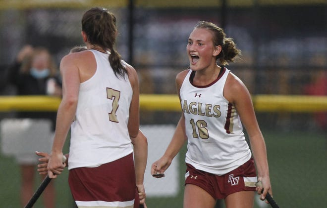 Molly Griffith (left) and Grace Cantwell celebrate a goal during the Watterson field hockey team's 2-all tie against visiting Thomas Worthington on Sept. 15. The Eagles are aiming for their second consecutive state championship.