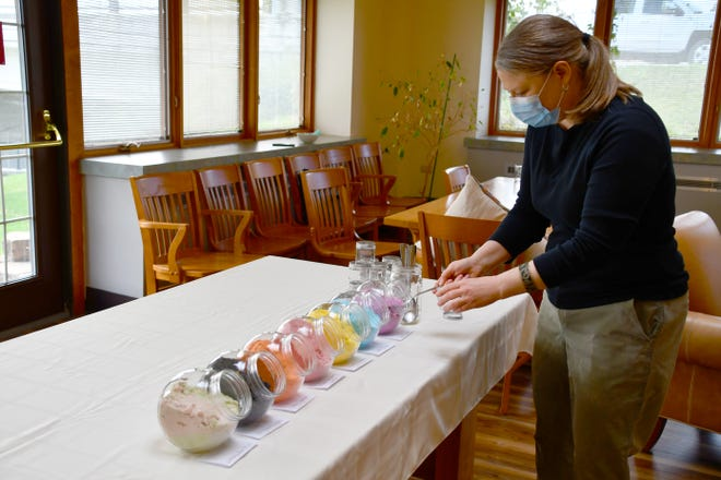 Real Good Bath & Body owner Carol Simmons shows guests how to layer bath salts after her presentation at the library