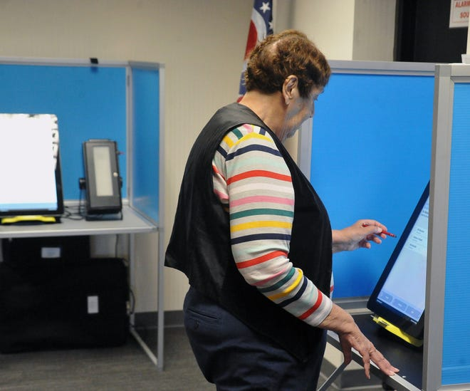 Helen Wright, a retired political science teacher from Orrville casts her vote.  She said she always voted on the first day so she could wear a sticker to her classroom.