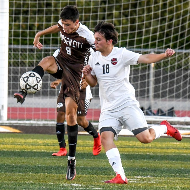 Garden City High School's David Hernandez, left, leaps in the air to move the ball upfield away from Wichita Heights Toller Phipps Monday at Buffalo Stadium.