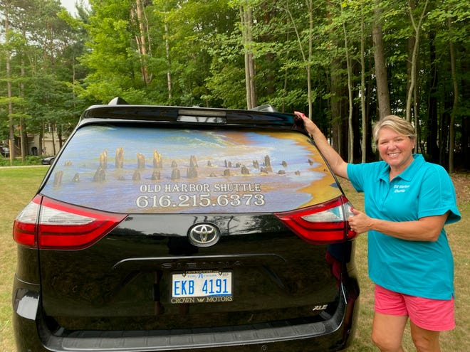 Julie Carten-Crandell poses for a photo with the Old Harbor Shuttle, a seven-passenger van that began offering alternative transportation along the lakeshore in June.