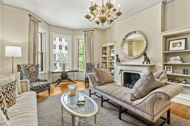 The living room fireplace is flanked by bookcases with display shelves on top and a bay window brings in the Back Bay's majesty.