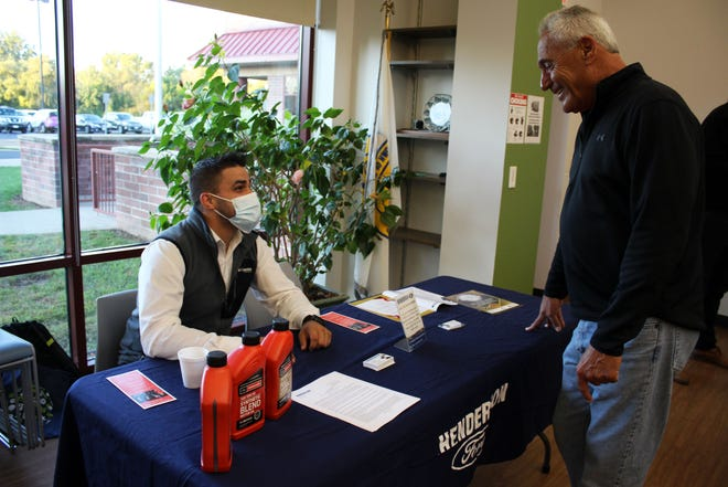Henderson Ford service manager Joe Monachino, left, speaks with SOHO Imaging owner Scott Gosert at the Webster Chamber of Commerce's monthly breakfast. The dealership presented oil change recommendations/tips and car industry updates, and provided a view of two new Ford Broncos.