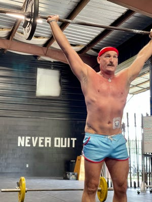 Todd Timmons, a cancer patient with Non-Hodgkins lymphoma, lifts a bar over his head at Militia Fitness in Crestview.