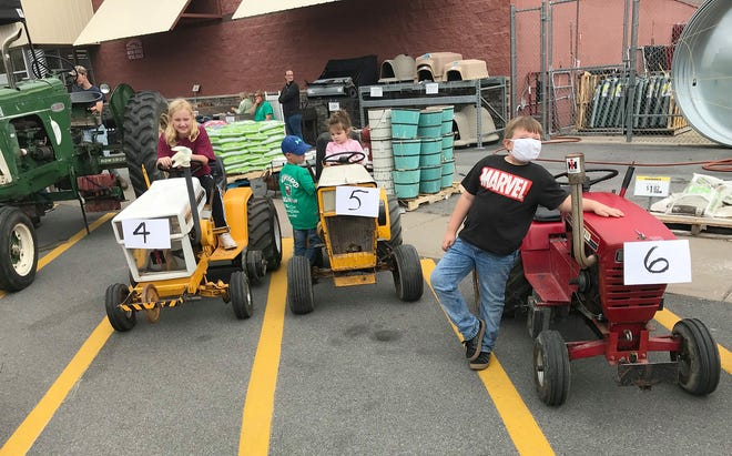 From left, Ally Shaw, Lucas Graham, Chloe Crandall and Noah Walker inspect the machinery Oct. 3 at the Tractor Show at Tractor Supply Co. in Hamilton.