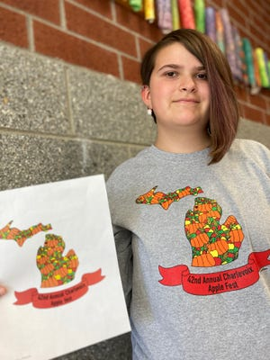 Natalie Kauffman, winner of the 2021 Apple Fest logo design contest, displays her winning design while wearing the festival's official t-shirt