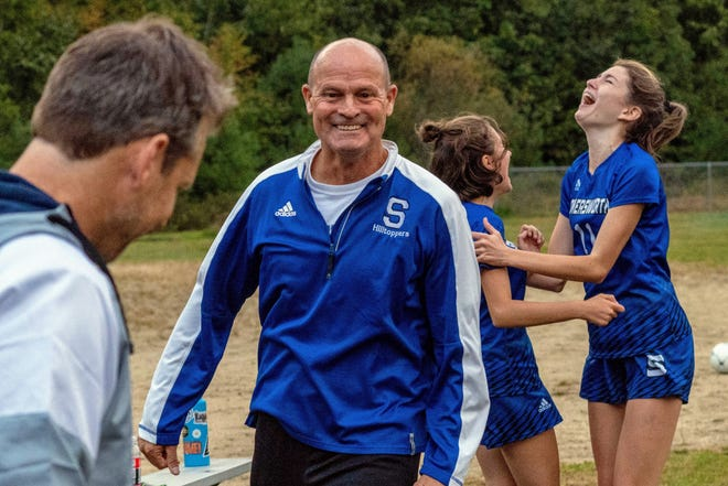 Somersworth High School girls soccer coach Mike Hill is all smiles as Ari Carter, left, and Audre Labelle celebrate behind him after last Friday's 2-1 double overtime win over Prospect Mountain. It was the first win of the season for the Hilltoppers.