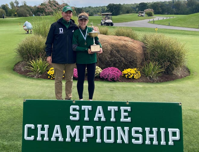 Dover High School golf coach Matt Fennessy presents the NHIAA girls golf individual championship trophy to his daughter, Dover freshman Carys Fennessy, on Saturday at Campbell's Scottish Highlands in Salem.