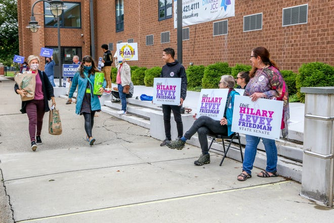 Advocates for the five candidates vying in the Democratic primary for the state Senate District 3 seat vacated by Gayle Goldin line up Tuesday along Elmgrove Avenue in Providence outside the polling station set up in the Jewish Alliance of Greater RI.