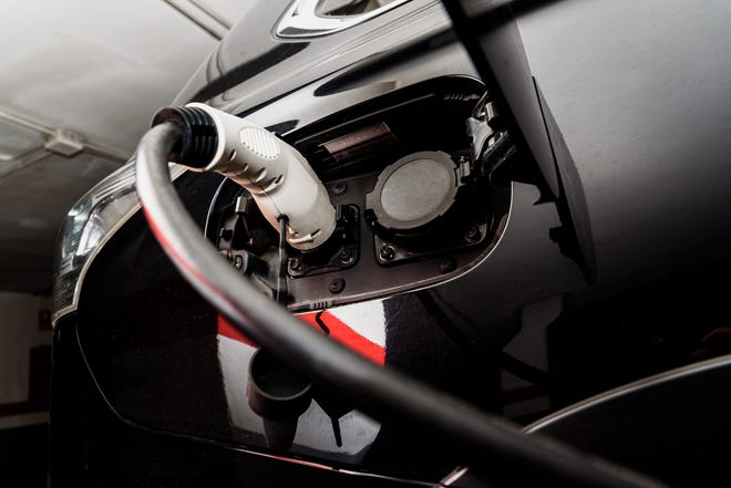 A car recharges its electric batteries inside a private garage with its own charging station.