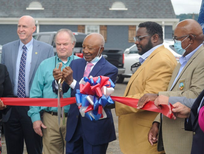 Dr. Clarence Underwood Jr. (with scissors) cuts the ribbon on Oct. 5 before unveiling a sign renaming the park across from the Gadsden Public Library after him.