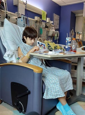 Kaleb Grezlik of Bowerston sits in his room at Akron Children's Hospital, where he is recovering from a life-threatening aftereffect of an unnoticed COVID-19 infection. His mother Cortney Grezlik posted the photo on social media Tuesday.
