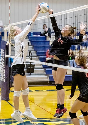 Sisseton's Chloe Langager (14) and Great Plains Lutheran's Bryn Holmen battle at the net during their high school volleyball match Monday night in Watertown. The visiting Redmen rallied to win 3-2.