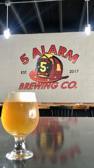 Three Lake Mills High School graduates and their former teacher opened 5 Alarm Brewing Co. in Lake Mills in 2017.