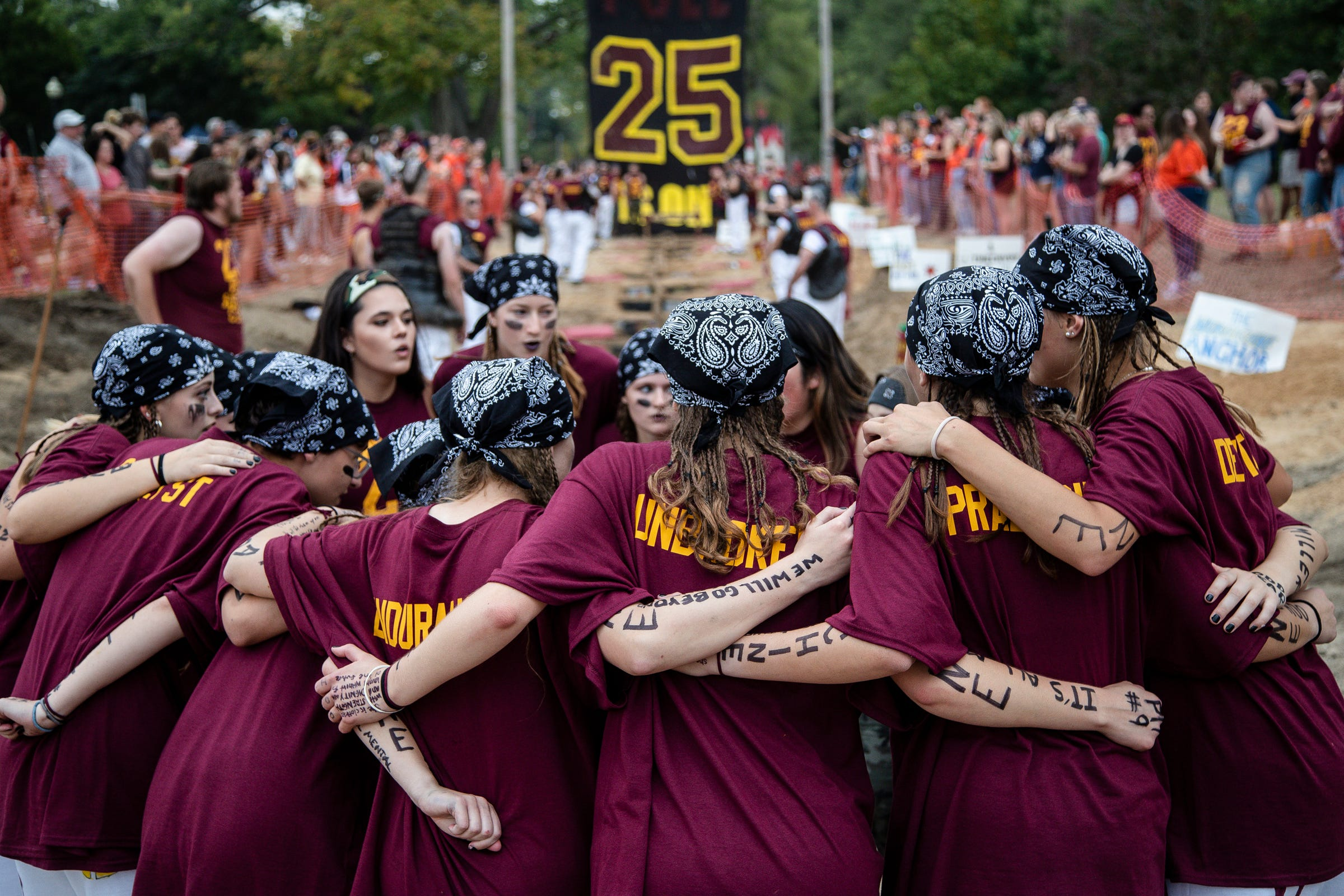 Odd-year morale boosters huddle before The Pull, an annual tug-of-war between the freshman and sophomore classes at Hope College in Holland on Saturday, Oct. 2, 2021.
