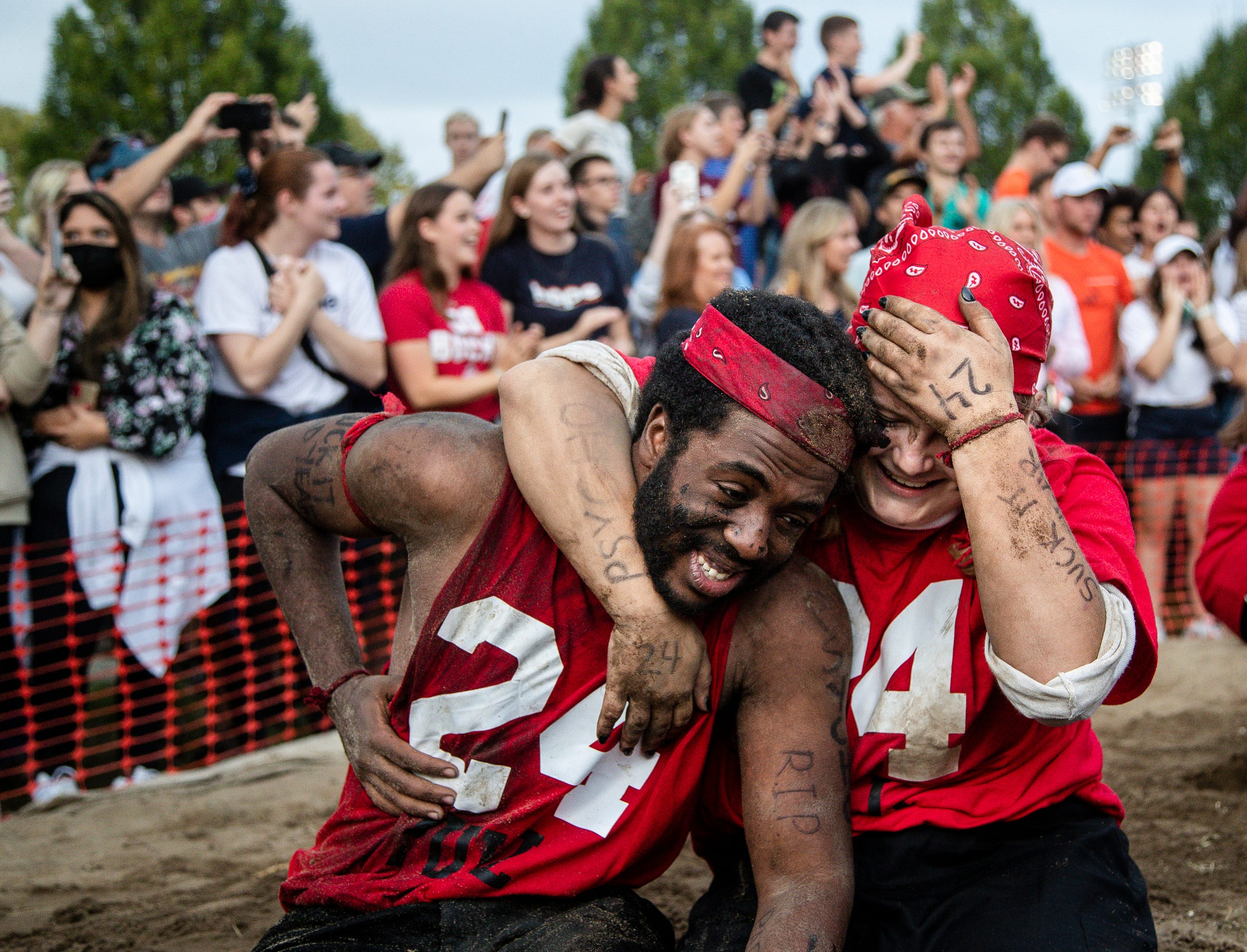 Even year puller Amadu Bah and morale booster Ruth Pasek climb out of the pit to celebrate their team's win over the odd year team during the Pull, an annual tug-of-war between the freshmen and sophomore classes at Hope College in Holland on Saturday, Oct. 2, 2021.