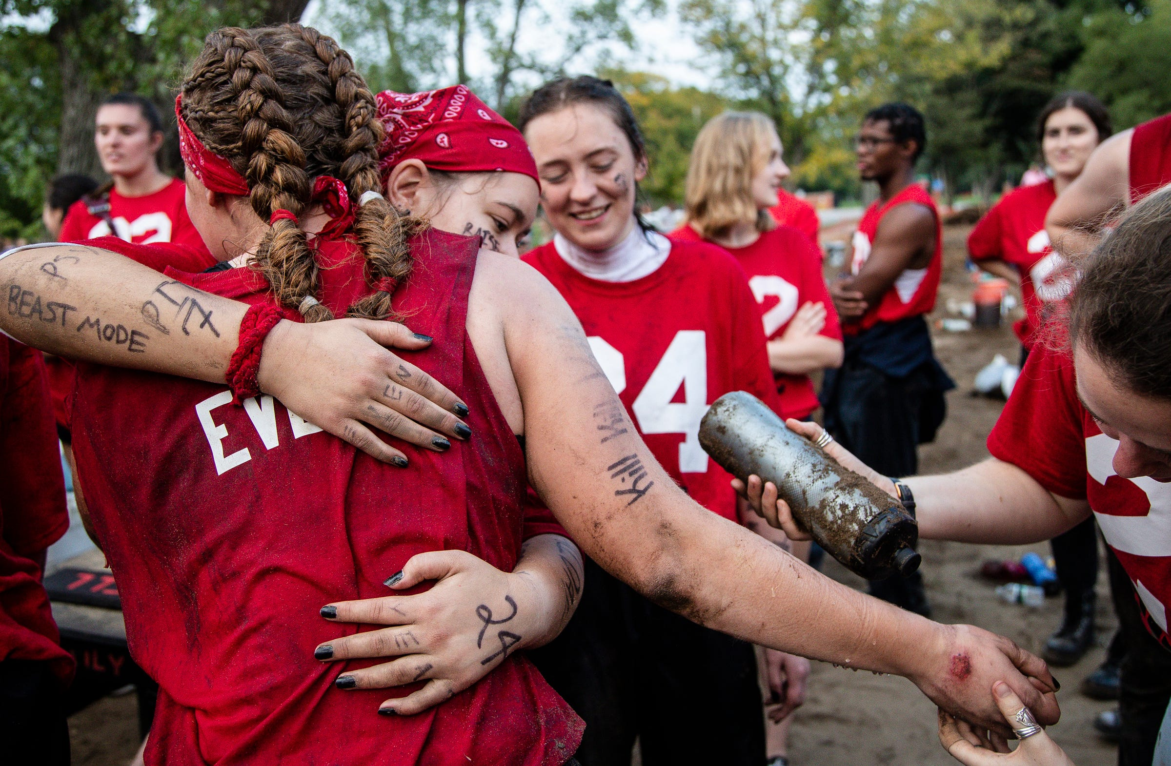 """Even year puller Lauren Tocco with a pit name """"Evel"""" is treated for the wound on her hand and congratulated by team members after defeating the odd year team at the Pull, an annual tug-of-war between the freshmen and sophomore classes at Hope College in Holland on Saturday, Oct. 2, 2021."""