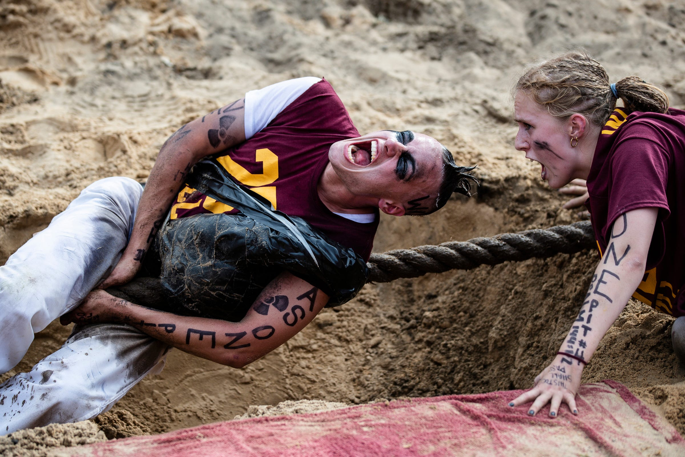 Odd year puller Jake Humbart holds on to the rope as morale booster Anna VanHuis shouts encouragement during the Pull, an annual tug-of-war between the freshmen and sophomore classes at Hope College in Holland on Saturday, Oct. 2, 2021.
