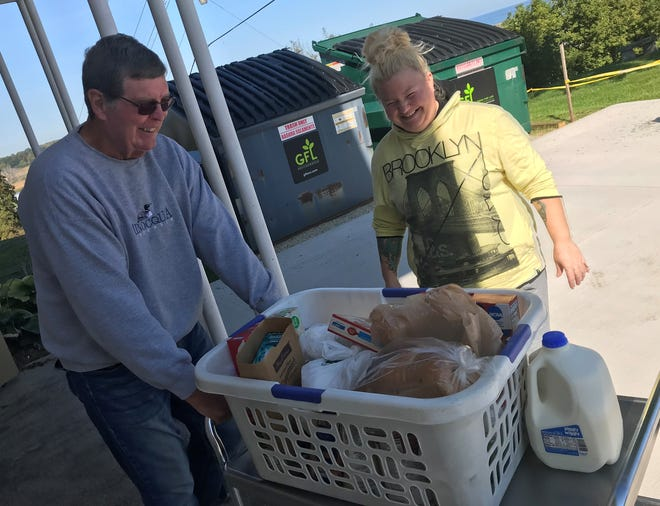 Dan Balch, treasurer for Lakeshore Community Pantry in Kewaunee, helps client Victoria Budzban with her supply of food and personal care items for the week.