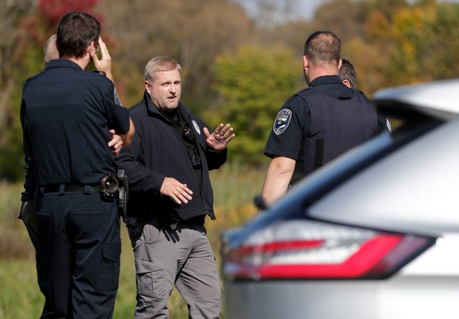 De Pere police gather at the corner of Tenmile and Black Earth drives near a feeder path to the East River Trail on Oct. 5, 2021, in De Pere, Wis.