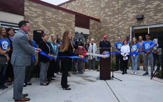 Alaiedon Elementary Principal Shana Barnum cuts a blue ribbon to mark the school's designation as a U.S. Department of Education Blue Ribbon School on Monday Oct. 4, 2021. Also pictured is Superintendent Ron Drzewicki, left.
