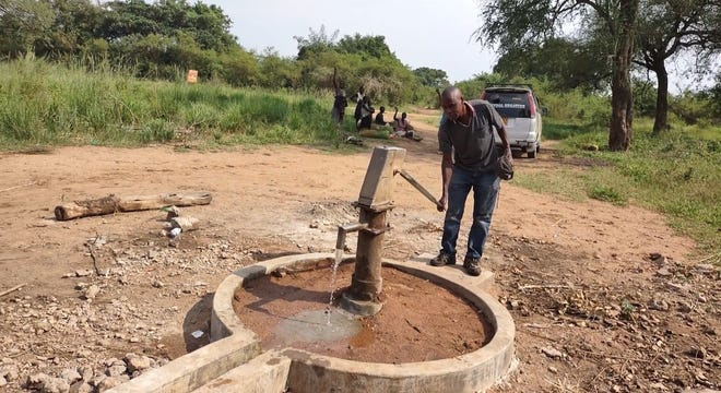 A man pumps water from a well near where Khaliku Kaba was born. Kaba, who lives in Lansing, crowdsourced money to fix the well.