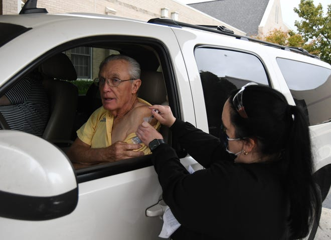 Thomas Reynolds of Mountain Home receives a flu shot Friday morning at Baxter County Health Unit's drive-thru flu vaccination event. The Health Unit is now offering flu shots on a walk-in basis.