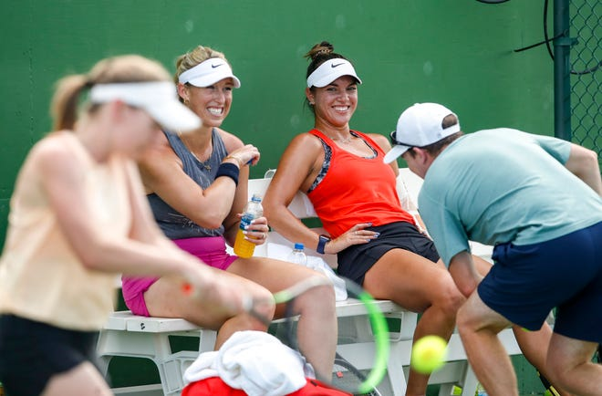 Desirae Krawczyk of Rancho Mirage laughs with her doubles partner Alexa Guarachi of Chile while talking with coach Craig Veal on the practice courts at the Indian Wells Tennis Gardens, Monday, Oct. 4, 2021, in Indian Wells, Calif.