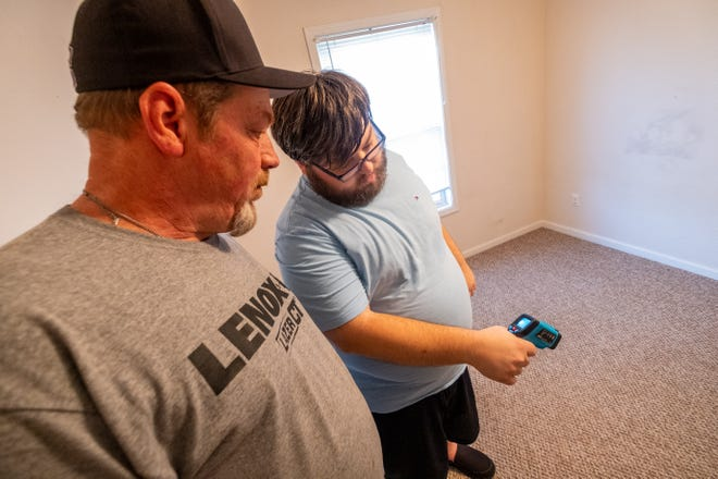 Chris Baker, founder of the Blue Water Paranormal Research team, right, teaches Jim Collins how to get a temperature base during a training session Monday, Oct. 4, 2021, at a Port Huron home.