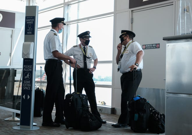 Pilots talk after exiting a Delta Airlines flight at the Ronald Reagan National Airport on July 22, 2020 in Arlington, Virginia. (Michael A. McCoy/Getty Images/TNS)