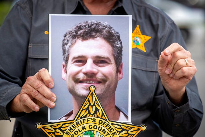 Polk County Sheriff Grady Judd holds up a photo of 39-year-old Shaun Runyon after he was captured after a 2-hour manhunt, Saturday, Oct. 2, 2021, in Davenport, Fla. Runyon was wanted in the death of co-workers who were attacked in a home he was sharing with them. (Ernst Peters/The Ledger via AP)