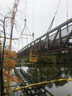 Construction workers build a new pedestrian bridge on the St. John's campus in Collegeville.