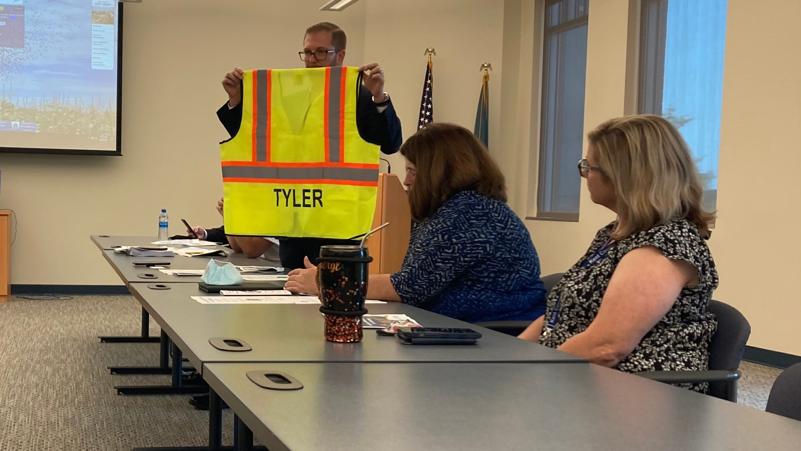 Michael McFarlane, a Tyler Technologies official overseeing Delaware's property tax reassessment effort, displays the vests surveyors are to wear when they visit homes and businesses as part of the process.