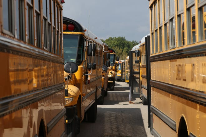School buses line up outside Zanesville High School after school recently. Districts in the area, and across the nation, are facing a driver shortage.