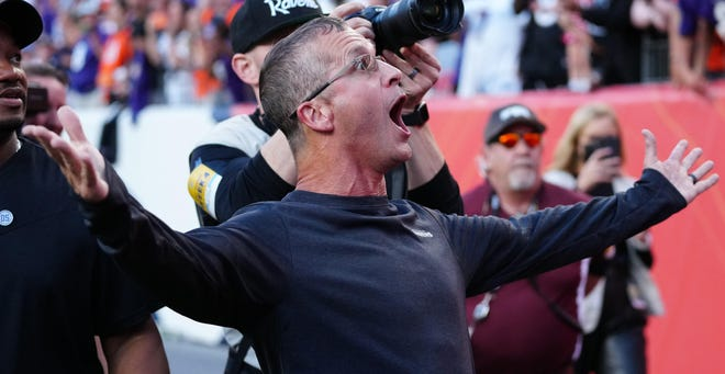 Head coach John Harbaugh of the Baltimore Ravens reacts as he sees a friend in the stands as he walks off the field after a 23-7 win over the Denver Broncos at Empower Field at Mile High on October 3, 2021 in Denver.