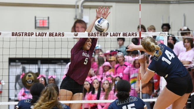 Bastrop's Crystal Creek (5) jumps up to make a block against Hendrickson.