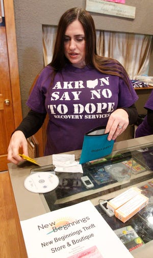 Tonia Wright, a board member and secretary of the group Akron Say No to Dope, opens a Project Dawn naloxone kit at the New Beginnings Thrift Store & Boutique in Akron's Kenmore neighborhood. The nonprofit has been selected to receive a $15,000 grant from the Summit County Opioid Healing Fund.