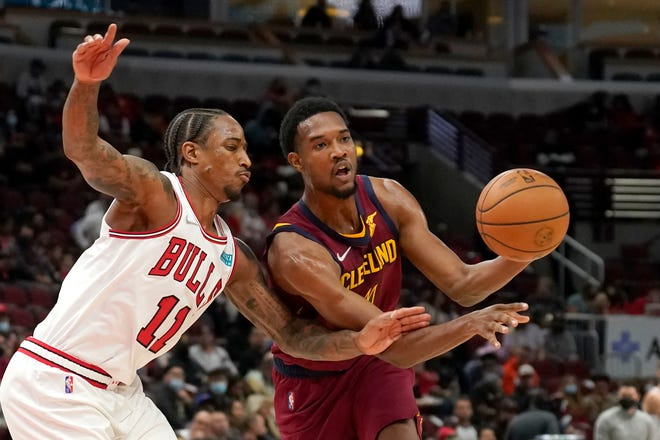 Cleveland Cavaliers' Evan Mobley, right, passes under pressure from Chicago Bulls' DeMar DeRozan during the first half of an NBA preseason basketball game Tuesday, Oct. 5, 2021, in Chicago. (AP Photo/Charles Rex Arbogast)