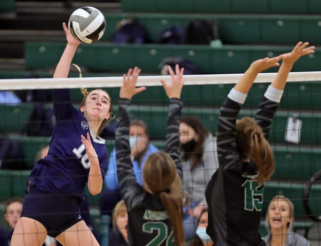 Hudson's Erica Kutchin, left, hits the ball over Nordonia's Katelyn Kellermann, center, and Irelynn Lavelle during the first set of a volleyball match, Tuesday, Oct. 5, 2021, in Macedonia, Ohio.