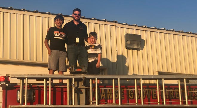 Children and city employees posed for a picture on top of the Orange Grove Fire Department.