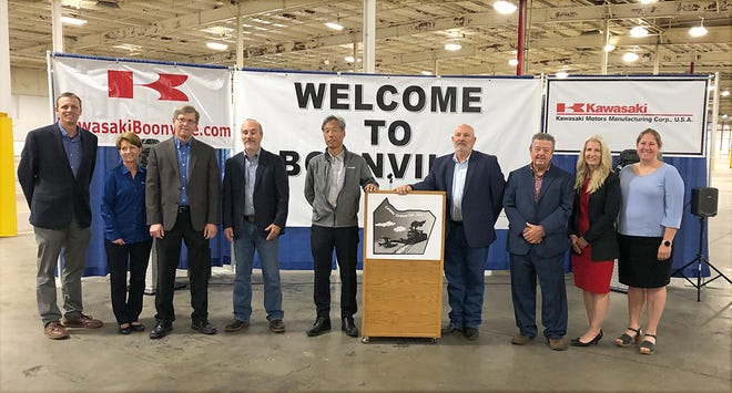 """Posing for a group picture after the announcement that Kawasaki Motors Manufacturing Corp., U.S.A. was opening a plant in Boonville are (left to right) Todd Sytsma, Anita Coulter, Mike Boyle, Chris Bramhall, Yutaka """"Joe"""" Tabata, Don Baragary, Ken Hirlinger, Gigi McAreavy, and Kate Fjell."""