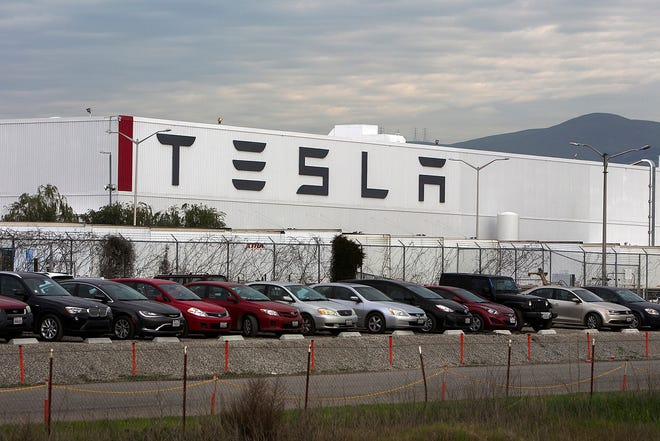 Cars are lined up near the Tesla Motors factory complex in Fremont, California. Tesla Inc. lost a case against a Black former elevator operator and must pay an unprecedented $137 million in damages.