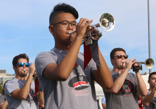 Hilliard Darby graduates from left Blake Hassay, 2020, Kyle Macatangay, 2019, and Luke Atkins, 2019, play with the Ohio State University Marching Band during practice Sept. 30.