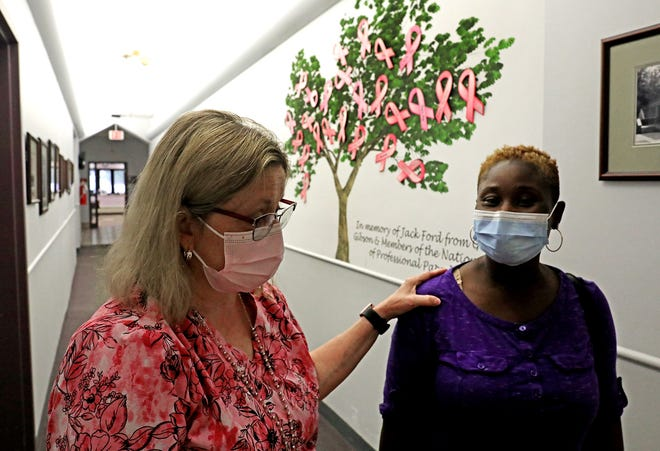 Mammography manager Caryn Halstead, left, leads Joyce Glover out of the room at the Columbus Cancer Clinic where Glover got a mammogram on Wednesday. The century-old cancer-screening center serves anyone no matter their ability to pay.