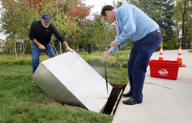 Steve Kidwell, acting superintendent for the city of New Albany's public services, and Scott McAfee, the city's communications and marketing director, lower New Albany's time capsule into its spot at Rose Run Park on Oct. 6. The capsule is supposed to stay put and unopened until 2071.