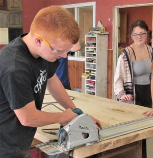 West Holmes sophomore Wyatt Schlauch uses a track saw to trim the edge of the white oak table top the building and trades class is making for the art room of the new Holmes Center for the Arts. Classmate Breanna Brichfield watches.