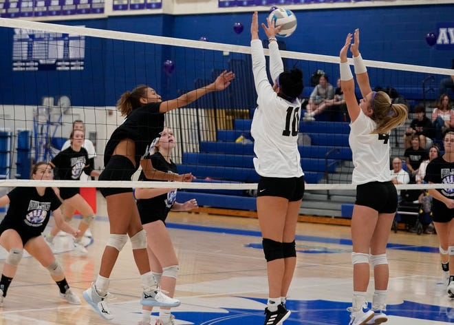Tecumseh's Jada Moore goes for a kill while Sofia Marcolonao (10) and Lauren Fraser (4) jump for a  block during Tuesday's match. [Telegram photo by Mike Dickie]