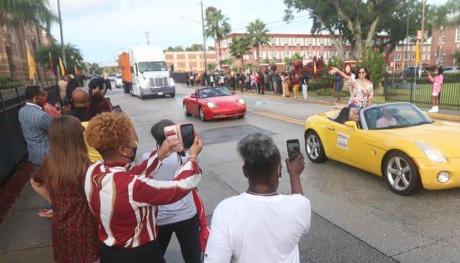 Master sculptor Nilda Comas waves to the crowd lining Mary McLeod Bethune Boulevard in Daytona Beach  on Wednesday, Oct. 6, 2021.
